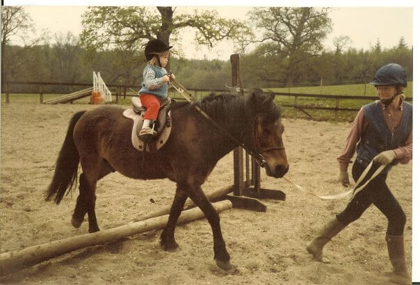Sarah White as a toddler riding a pony over a small jump