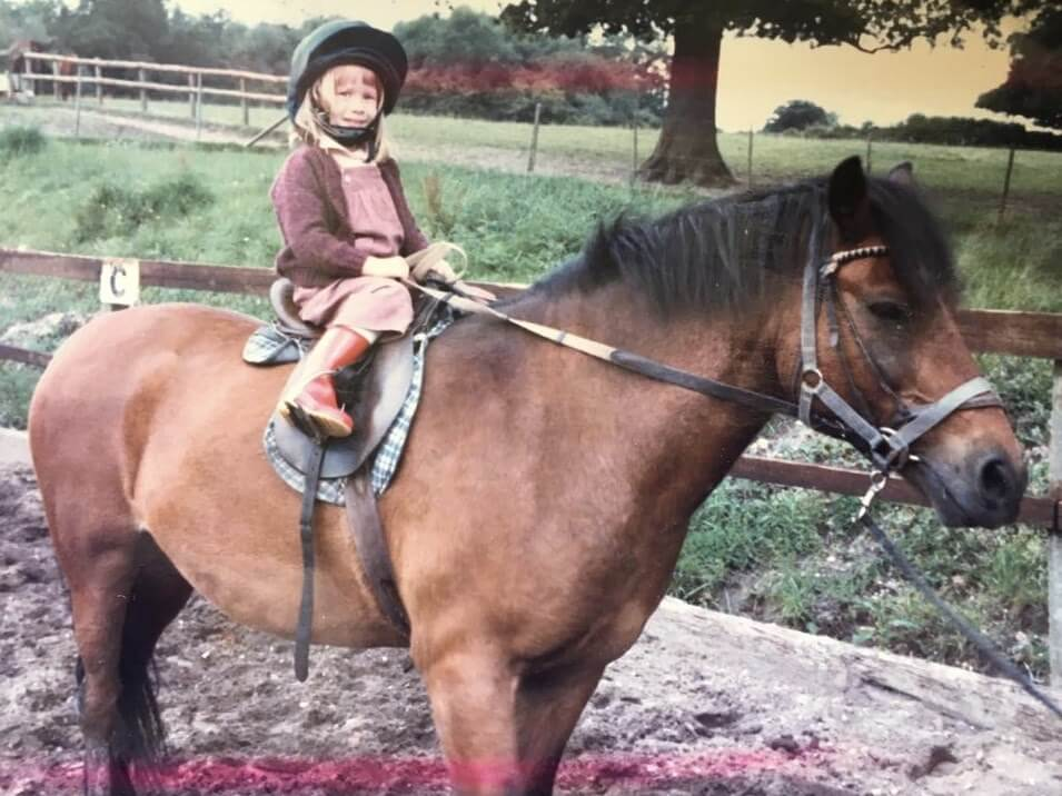 Sarah White as a toddler sitting on a pony