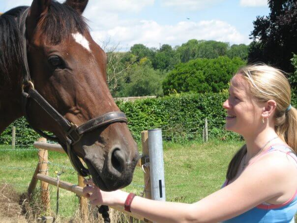 Sarah White smiling holding a horse
