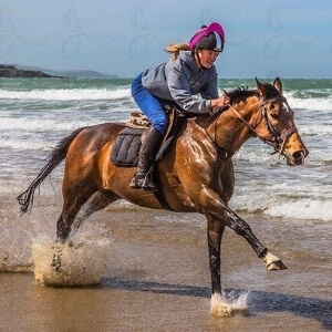 Sarah White galloping on a bay horse on a beach