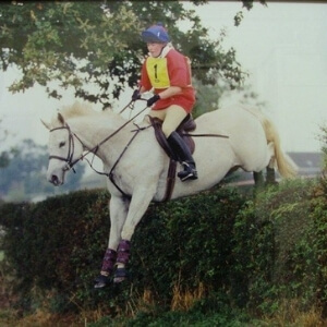 Sarah White landing over a hedge on a grey horse