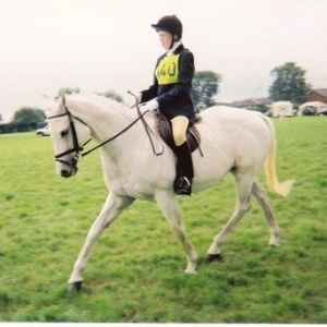 Sarah White trotting on a grey horse