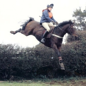 Sarah White flying over a hedge on a bay horse