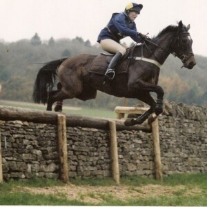 Sarah White jumping a bay horse over a stone wall